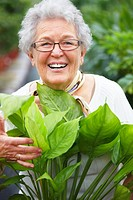 Closeup portrait of a happy woman standing with plants and smiling