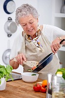 Mature old woman holding a pan and preparing food in kitchen
