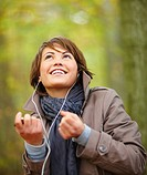 Portrait of a beautiful smiling woman listening to music and dancing