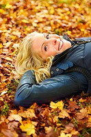 Closeup portrait of a woman lying on ground covered with leaves and smiling