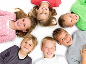 Closeup portrait of young boys and girls lying in a circle on floor isolated on white background