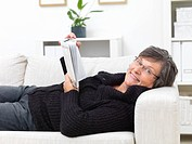 Happy senior woman lying on a sofa and reading book