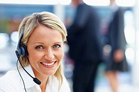 An attractive call centre executive with a headset, smiling