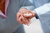 Closeup of an elderly woman´s hand being held by a doctor , focus on hands