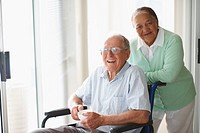 Portrait of a happy elderly couple at a hospital , man on the wheelchair