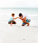 Father and son at the sea shore listening to a seashell
