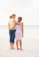 Beach vacation _ Rear view of a mother and daughter standing together at the sea shore