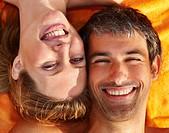 Beach picnic _ Closeup portrait of a happy couple lying on a towel
