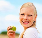 Portrait of a happy young female eating a green apple outside