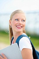 Sweet young college student holding a folder and smiling outdoors