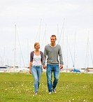 Full length of a young couple holding hands and walking on a grass field, harbour view in the background