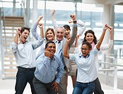 Business success _ Happy multi ethnic executives with hands raised