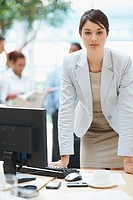 Confident young business woman at desk with colleagues in the background