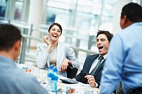 Business colleagues laughing on a funny joke cracked during the meeting