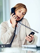 Portrait of surprised mature businesswoman multitasking by handling telephone calls