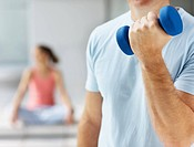 Mid section of a man exercising with a dumbbell at the gym