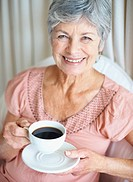 Closeup portrait of a retired smiling senior woman drinking coffee
