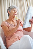 Thoughtful senior woman solving a crossword puzzle in newspaper at home