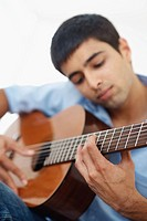 Young male musician playing a guitar isolated against white background