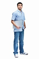 Full Length portrait of a young man holding a laptop over white background