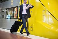 Businessman walking on a platform next to a train, Stockholm, Sweden.