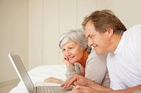 Smiling senior couple using a laptop while lying on the bed