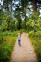 Boy playing with a stick in a forest, Sweden.