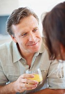 Closeup of a mature man with a juice glass talking to a woman