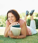 Happy middle aged woman with a book lying on grass at the lawn