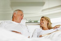 Beautiful smiling couple looking at each other while relaxing In bed at home