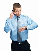 Handsome Caucasian business entrepreneur looking at watch while talking on cellphone