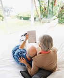 Rear view of a relaxed senior man and woman reading newspaper on bed
