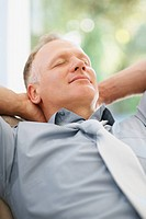 Relaxed middle aged business man relaxing with hands behind head