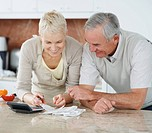 Smiling elderly couple calculating their shopping bills at home