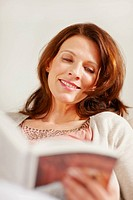Pretty relaxed middle aged brunette reading book on a couch
