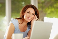 Portrait of a cheerful middle aged brunette with a coffee cup and laptop in front