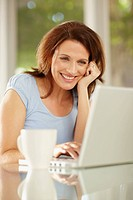 Cheerful middle aged brunette using a laptop