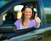 Happy woman with her new car showing thumbs up sign