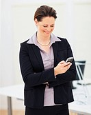 Happy mature business woman reading a text message on cellphone at work