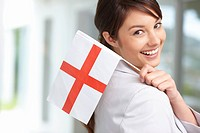 Pretty young female holding an English flag , smiling