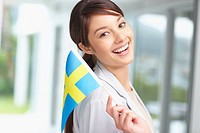 Portrait of a beautiful young woman holding a swedish flag