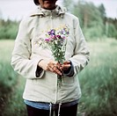 Woman with a nosegay of meadow flowers, Sweden.