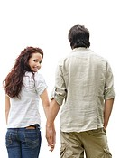 Rear view of a young couple against white _ Female looking at you with a smile
