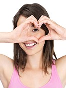 Cute young female making a heart shape with hands against white