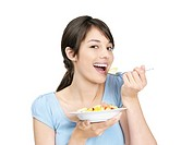 Portrait of a young casual female enjoying a bowl of fresh fruits isolated against white