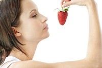 Profile view of a young female holding up a fresh strawberry against white