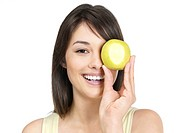 Portrait of a happy young lady holding a green apple infront of eye