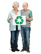 Portrait of a senior couple holding recycle sign on white background