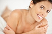 Closeup portrait of a happy young naked woman smiling