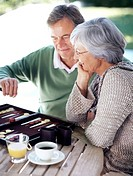 Smiling old couple busy playing a game of backgammon